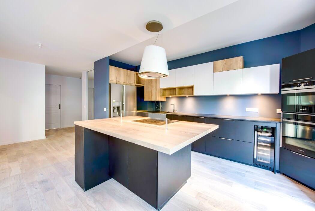 Zoom sur l'îlot central de cette cuisine haut de gamme et très design mêlant gris et bois massif