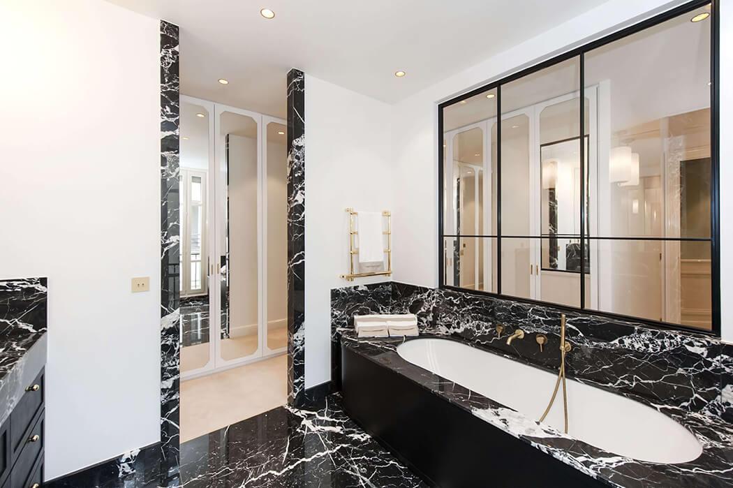 baignoire avec robinetterie de luxe et verrière pour cette salle de bain