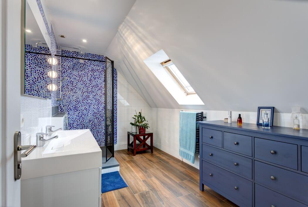 Salle de bain ambiance bord de mer avec commode bleue, parquet pont de bateau, et douche à l'italienne