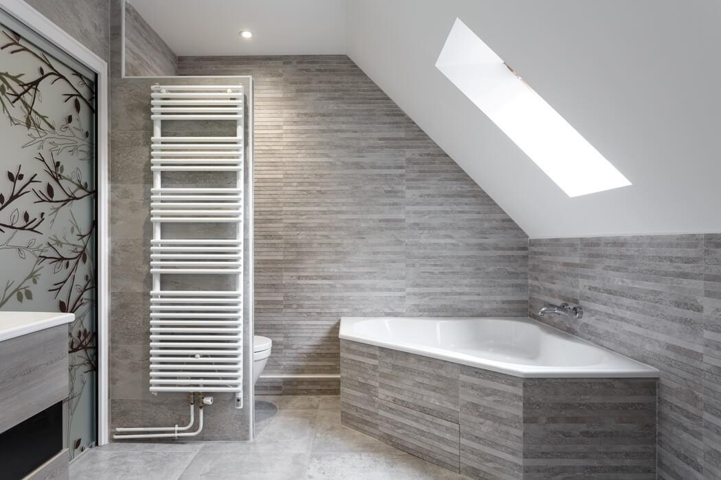 Une belle baignoire d'angle aux tons gris dans cette salle de bain rénovée