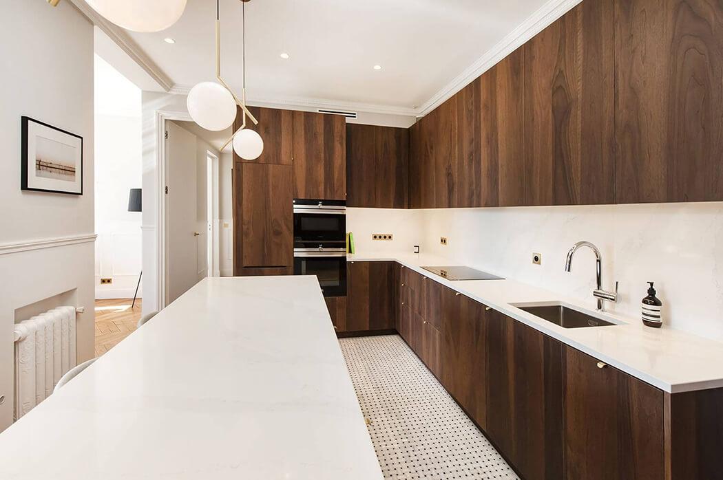 cuisine de luxe en bois exotique dotée d'une grande table familiale et de jolis luminaires en suspension