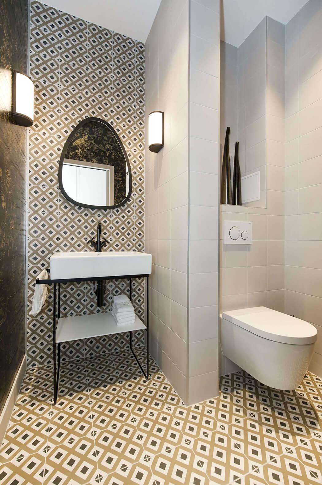 salle de bain haut de gamme très tendance avec carreaux de ciment, appliques murales et wc suspendus
