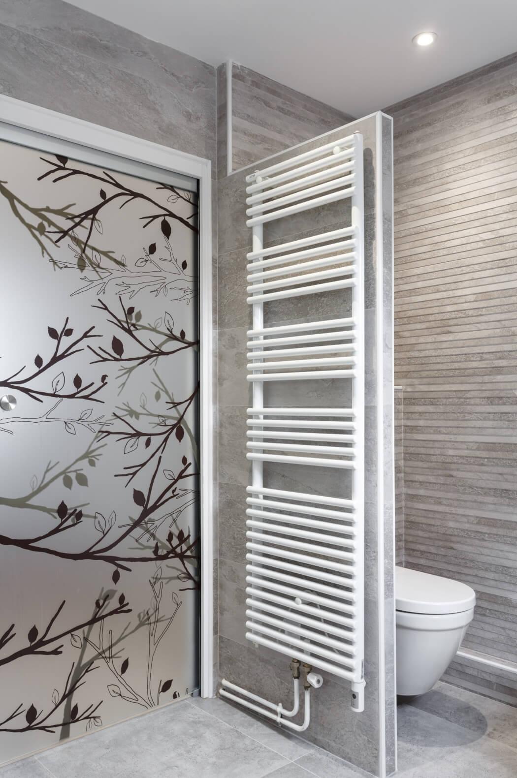 WC suspendu et sèche serviette haut de gamme dans cette salle de bain rénovée aux tons gris