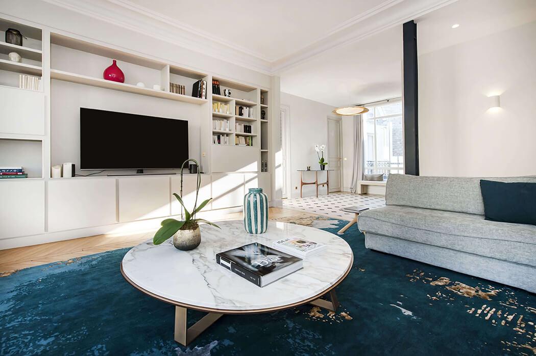 rénovation salon haut de gamme avec tapis bleu vert, canapé gris clair, bibliothèque sur-mesure