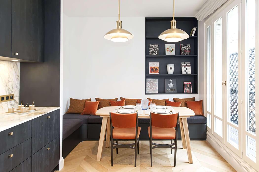 coin repas aménagé dans cette cuisine haut de gamme en bois avec crédence et plan de travail en marbre