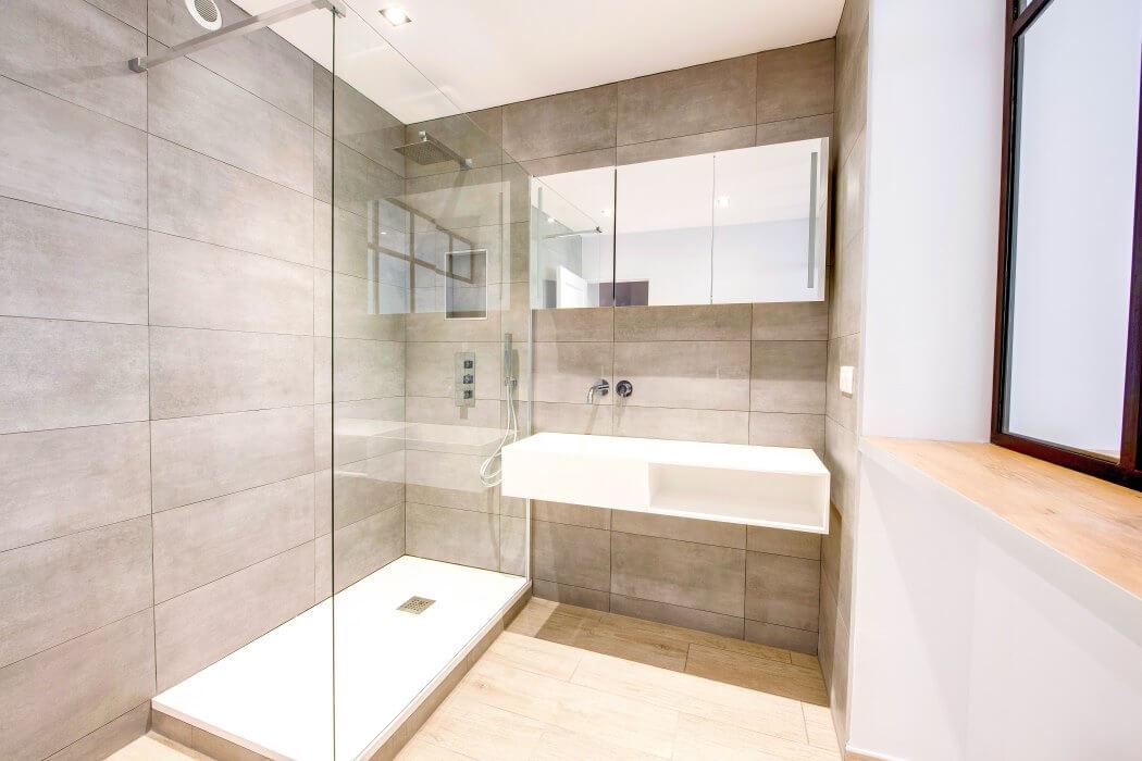 Salle de bain aux tons naturels, avec douche à l'italienne et lavabo