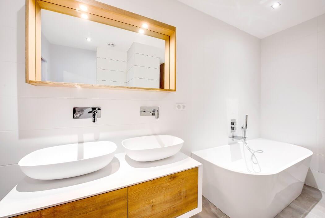 Salle de bain tons naturels (blanc, bois et gris) avec lavabos aux formes arrondies rappelant celles de la baignoire