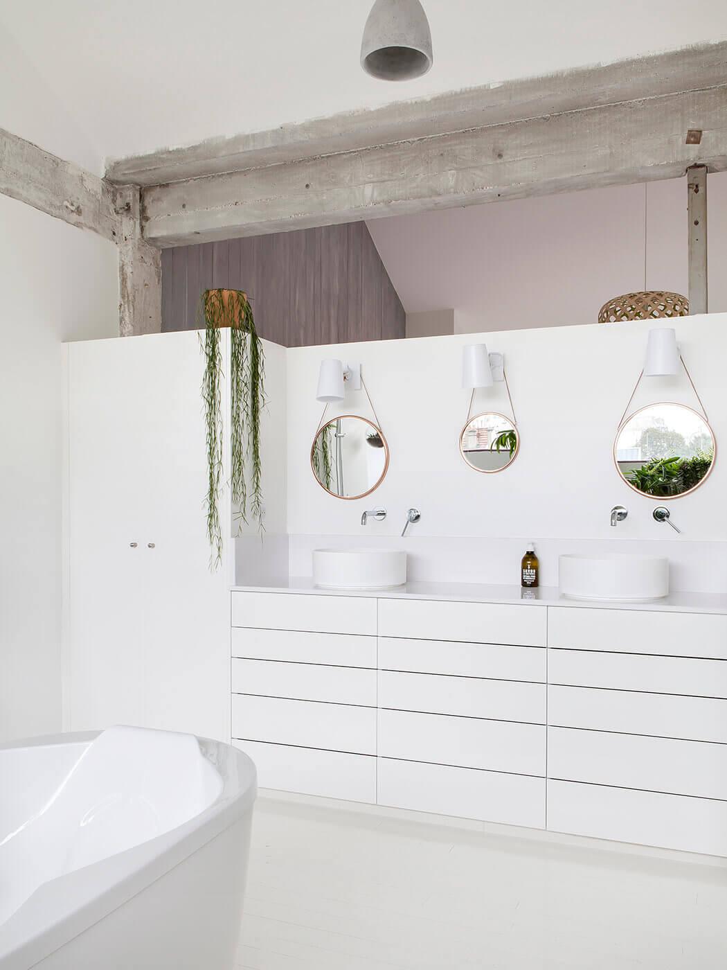 Mélange de modernisme et d'authenticité, avec cette salle de bain au blanc immaculé et ses poutres apparentes