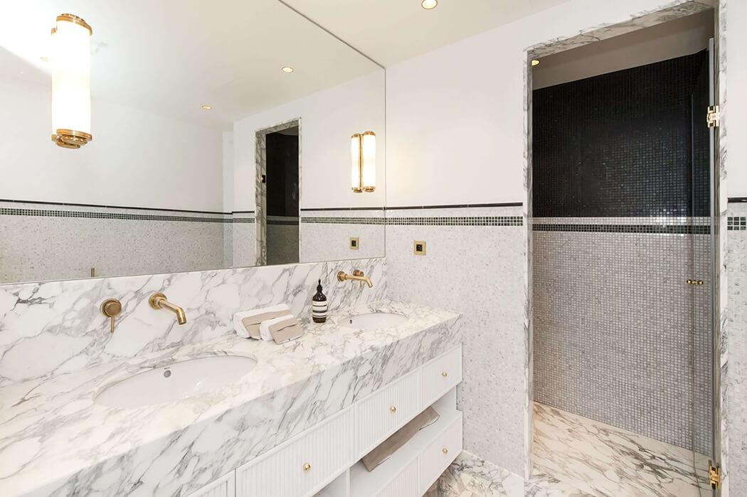 salle de bain avec double vasque en marbre surmontée d'un grand miroir, et équipée d'une douche à l'italienne