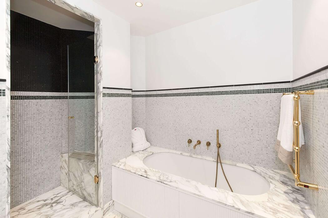 la robinetterie de cette salle de bain de luxe marbre / mosaïque s'associe parfaitement avec le porte-serviette cuivré